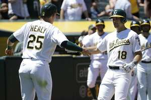 Oakland Athletics' Chad Pinder (18) is congratulated after hitting a two-run home run that scored Ryon Healy (25) against the Boston Red Sox during the fourth inning of a baseball game in Oakland, Calif., Sunday, May 21, 2017. (AP Photo/Jeff Chiu)