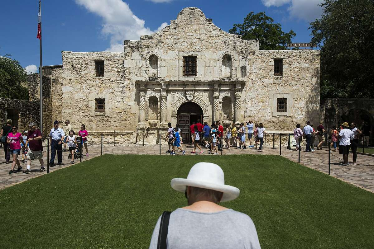 A woman reads a plaque in front of The Alamo as tourists make their entrance into the building on Friday, June 10, 2016.