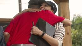 Freddy Rosario, hugs Gabrielle Rapport, co-founder and executive director of Operation Tiny Home after Operation Tiny Home presented Rosario with his new home, Saturday, May 20, 2017 at Warren High School.