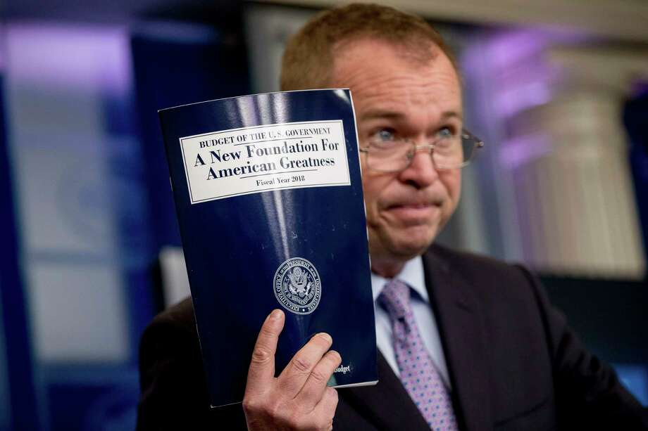 Budget Director Mick Mulvaney holds up a copy of President Donald Trump's proposed fiscal 2018 federal budget as he speaks to members of the media in the Press Briefing Room of the White House in Washington, Tuesday, May 23, 2017. (AP Photo/Andrew Harnik) ORG XMIT: DCAH204 Photo: Andrew Harnik / Copyright 2017 The Associated Press. All rights reserved.