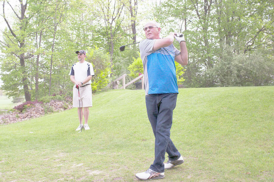 THEOPHIL SYSLO | For the Daily News Philippe Escoffre, of France, tees off while golfing with his son Laurent Escoffre (left), of Midland, at Sandy Ridge Golf Course last week. Philippe Escoffre shot his first hole in one on May 15 at Sandy Ridge while golfing with Laurent.