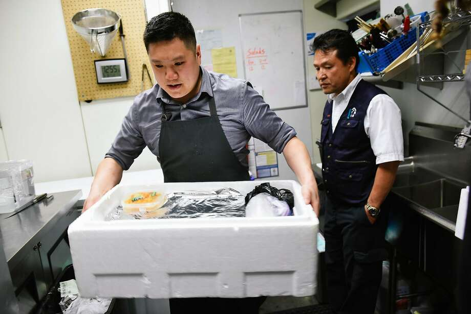 Geoffrey Lee (left), chef and co-owner of Ju-Ni restaurant in S.F., carries a box of fish from Tsukiji Market in Tokyo just delivered by fish importer Yoshi Takahashi (right). Photo: Michael Short, Special To The Chronicle