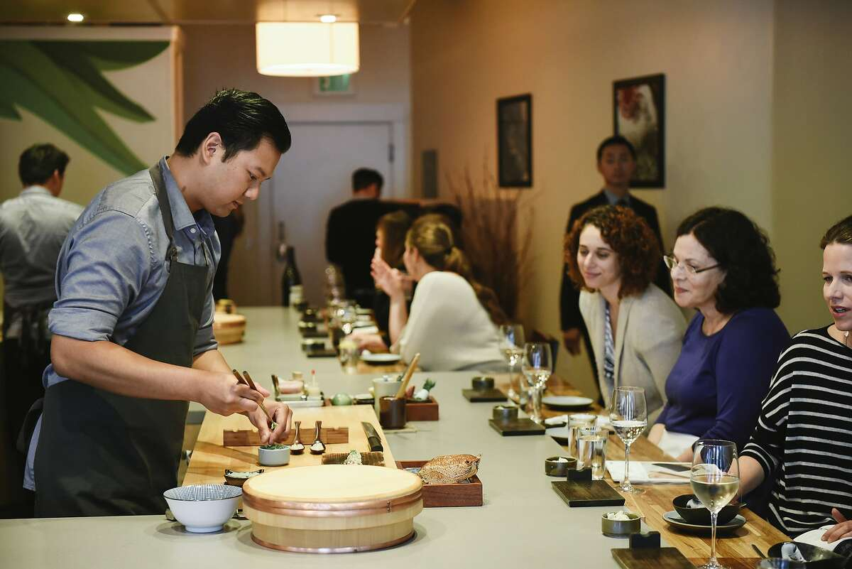 At Ju-Ni restaurant: Chef Daniel Realin makes sushi for guests at the counter.