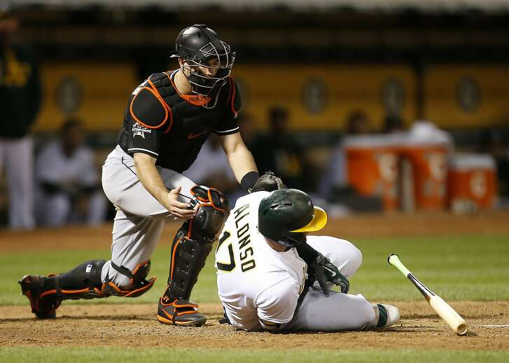 Oakland Athletics' Yonder Alonso falls to the ground after being hit by a pitch from Miami Marlins relief pitcher Jarlin Garcia during the sixth inning of a baseball game on Tuesday, May 23, 2017, in Oakland, Calif. (AP Photo/Tony Avelar)