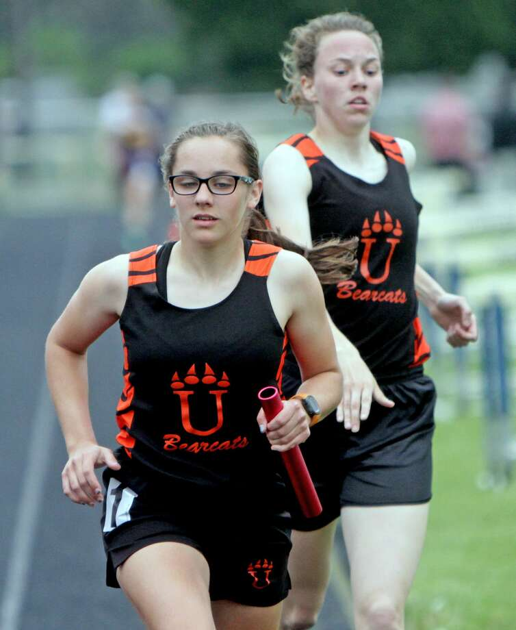 Ubly's Janelle White hands off to teammate Haili Gusa in the 3,200 relay, during the Huron Daily Tribune Meet of Champions. The duo is qualified for eight events, in Saturday's Division 4 State Finals, Saturday, at Houseman Field, in the Grand Rapids Area. Photo: Paul P. Adams/Huron Daily Tribune