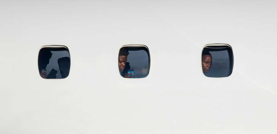 Rodney Green, 14 (center), and Nikya Bard Blake, 14 (right), peer from their windows as the 30-passenger jet taxis to the runway at Buchanan Field in Concord. Photo: Paul Kuroda, Special To The Chronicle