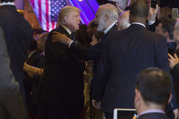 President Donald Trump greets Carl Icahn, billionaire activist investor (center right) as he arrives at an election night event in New York on April 19, 2016.
