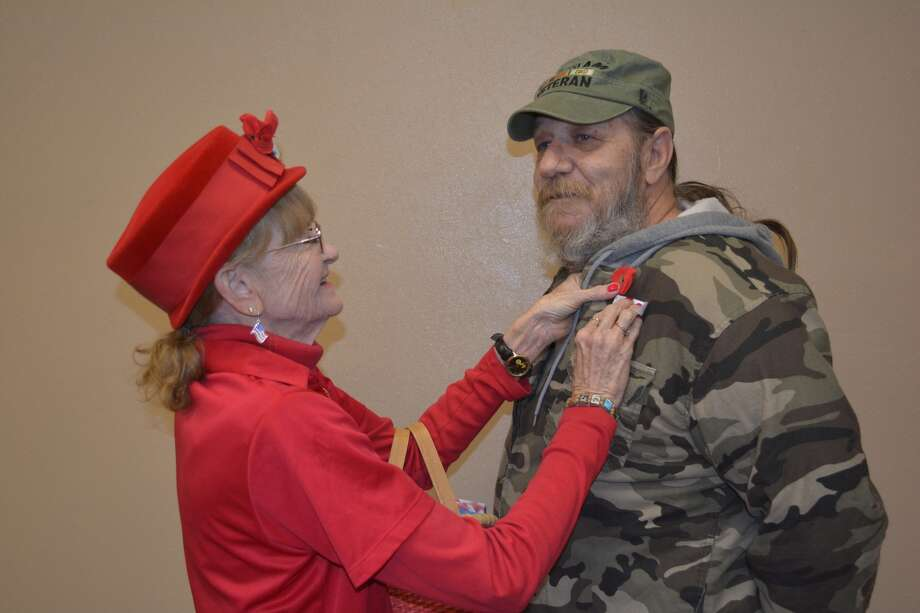 Jerree McKeeman, president of American Legion Auxiliary Unit 260, pins a poppy on the jacket of her husband, Marc McKeeman, U.S. Air Force veteran who served in Vietnam in 1971-72. Auxiliary members will be distributing poppies on Friday, May 26, at United Supermarket and Amigos. All donations benefit veterans, their families and active duty personnel.