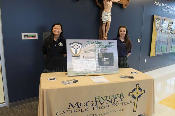 Freshman Faith Scott, left, and junior Amaree Moss welcomed guests Tuesday night to Father McGivney Catholic High School's Open House and Media Night.