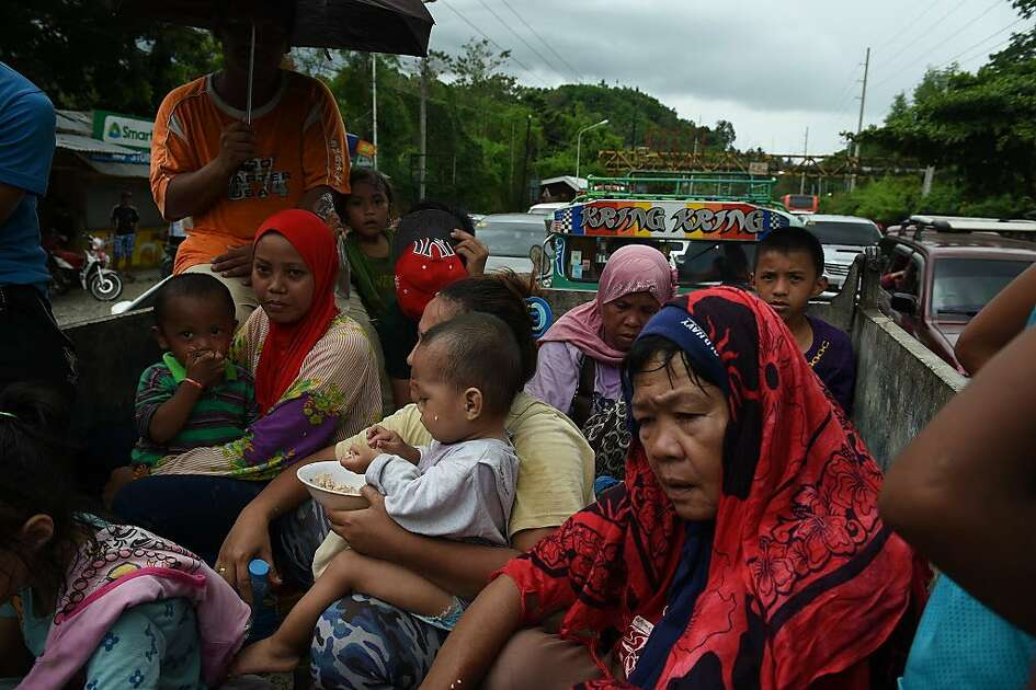 "Resident fleeing from Marawi city,where gunmen who had declared allegiance to the Islamic State group rampaged through the southern city, are cramped on a truck as they traverse a traffic gridlock near a police checkpoint at the entrance of Iligan City, in southern island of Mindanao on May 24, 2017. Philippine President Rodrigo Duterte warned that martial law would be ""harsh"" and like a dictatorship, after imposing military rule in the south of the country to combat Islamist militants. / AFP PHOTO / TED ALJIBETED ALJIBE/AFP/Getty Images"