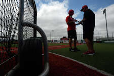 Lamar's Trey Silver, left, shows his bat to Scott Halten during practice on Tuesday. The Cardinals will play 8th seeded in this week's Southland Conference.  Photo taken Tuesday, May 23, 2017 Guiseppe Barranco/The Enterprise