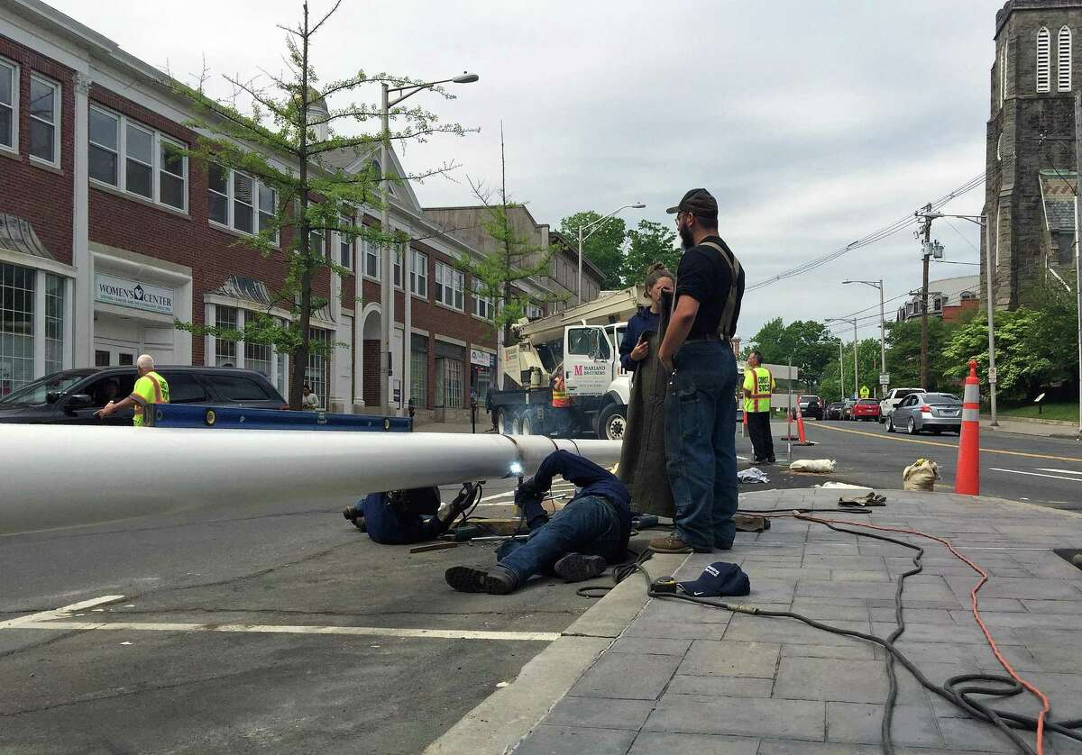 Workers assemble the final piece of a 100-foot flagpole in dowtown Danbury.