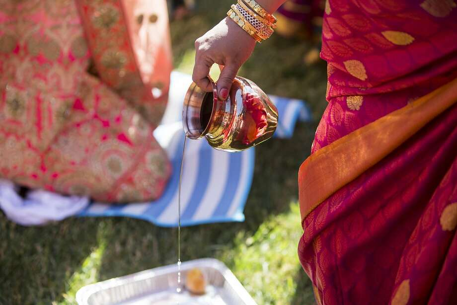 Water is poured during the oonjal part of the wedding ceremony. Photo: Laura Morton, Special To The Chronicle
