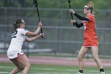 New Canaan High School's Caroline Schuh tries to block the pass of Ridgefield High School's Caeleigh Tannian in the FCIAC girls lacrosse semifinals played at Norwalk High School on Monday. Ridgefield upset New Canaan, 14-11.