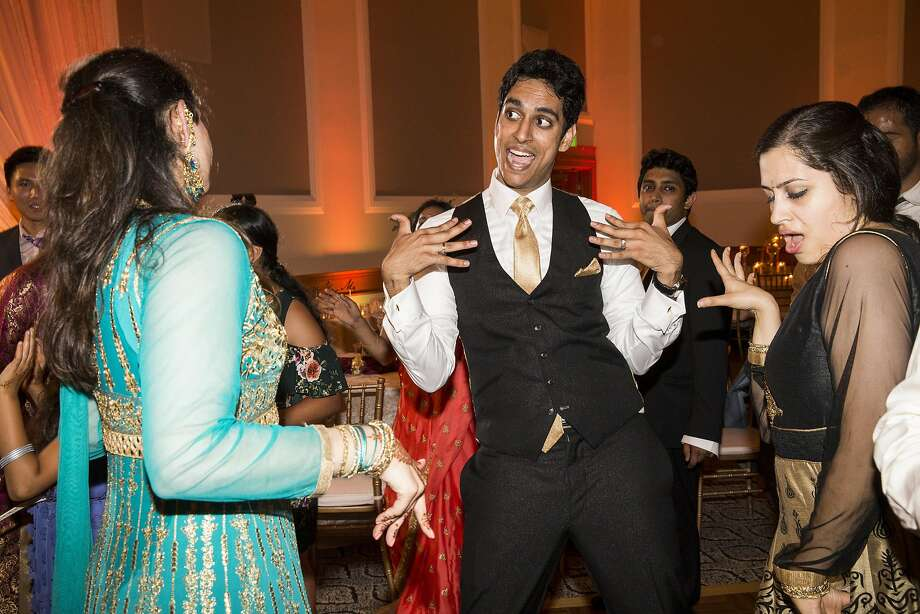 Priam Mukundan (center) dances with his sister Preethi Mukundan (left) and cousin Ramya Rangamannar (right) during his wedding. Photo: Laura Morton, Special To The Chronicle