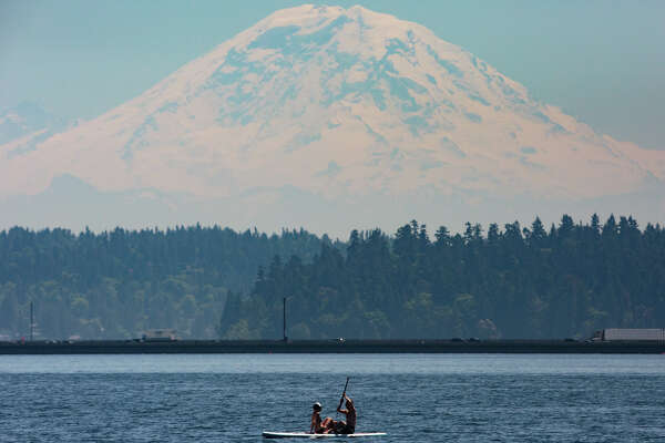 A couple on a paddle board is treated to a clear view of Mt. Rainier, seen from Madrona Beach on Tuesday, May 23, 2017.