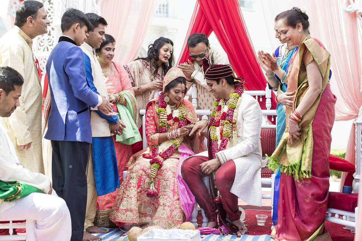 Priam Mukundan (right) puts the wedding ring on bride Rucha Heda's finger during their Hindu wedding ceremony.