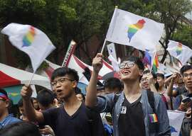 Same-sex marriage supporters wave rainbow Taiwan flags after the Constitutional Court ruled in favor of same-sex marriage outside the Legislative Yuan in Taipei, Taiwan, Wednesday, May 24, 2017. Taiwan's Constitutional Court ruled in favor of same-sex marriage on Wednesday, making the island the first place in Asia to recognize gay unions. (AP Photo/Chiang Ying-ying)