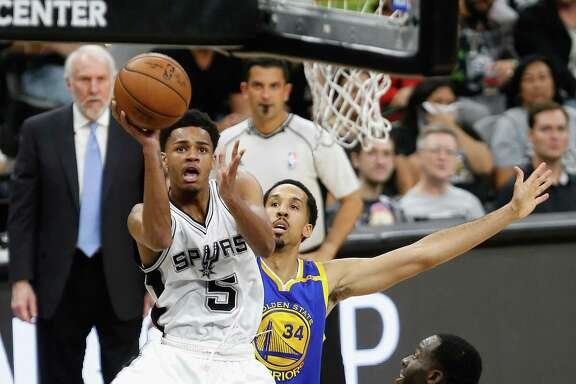 Spurs' Dejounte Murray shoots a layup — with coach Gregg Popovich watching from the sideline — against the Golden State Warriors' Shaun Livingston in the first half of Game 4 of the Western Conference finals at the AT&T Center on May 22, 2017 in San Antonio.