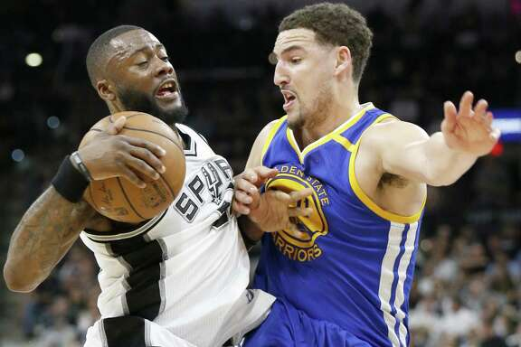 Spurs' Jonathon Simmons looks for room around the Golden State Warriors' Klay Thompson during second half action in Game 4 of the Western Conference finals on May 22, 2017 at the AT&T Center.