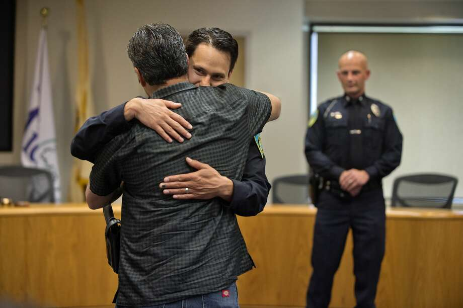 Newly sworn in Midland Police Officer Jose DeLeon gives his father Robert DeLeon a hug during an officer swearing-in ceremony at City Hall Wednesday afternoon. DeLeon, was joined by James Burchfield II and Christopher Hurst as new officers to the City of Midland Police Department. Photo: Brittney Lohmiller/Midland Daily News/Brittney Lohmiller