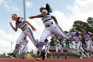 Willis third baseman Samara Lagway, right, races starting pitcher Casey Dixon warms up before Game 2 of a Region III-5A semifinal series Friday, May 19, 2017, in Willis.