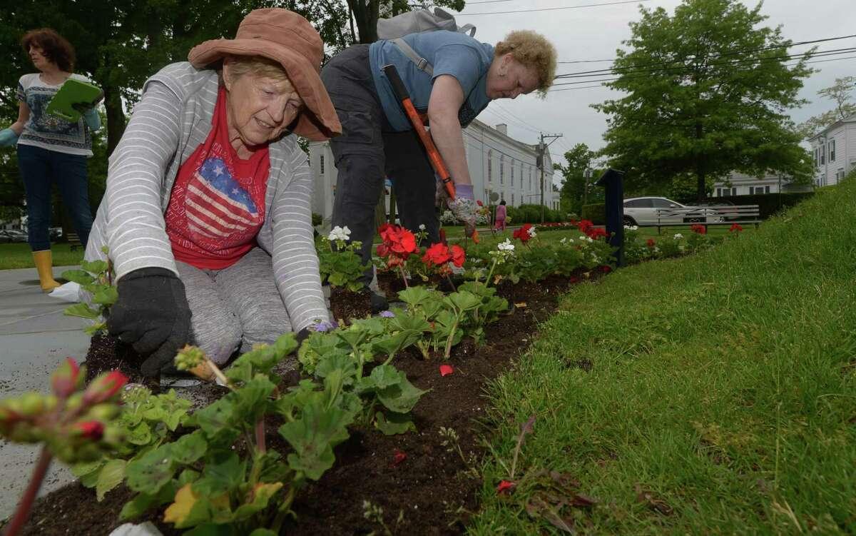 Norwalk Garden Club members including Betsy Kondub and Jennifer Rumbelow plant flowers around the gazebo, flag, and veteran's memorial on the Norwalk Green Wednesday, May 24, on behalf of the First Water District in Norwalk.