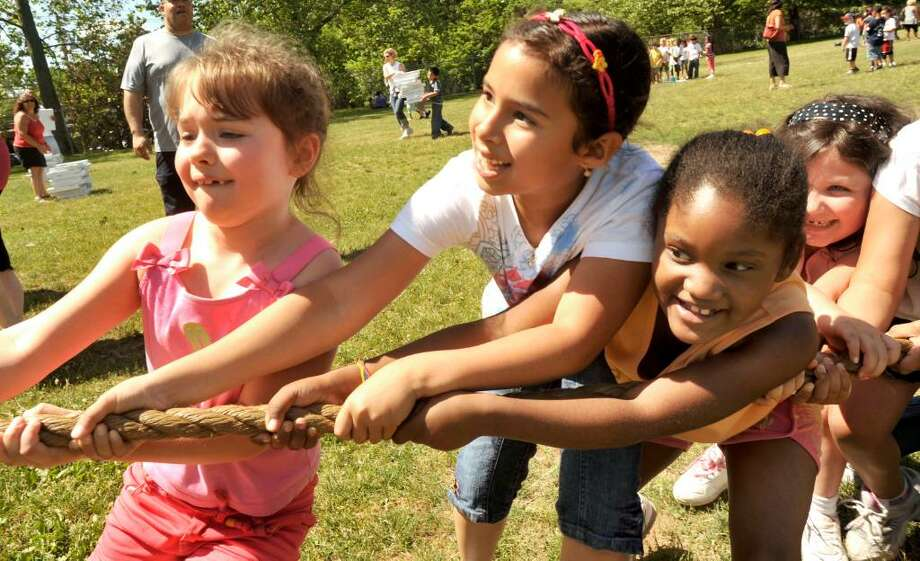 First-graders including Melody Barz, left, Valentina Ramos, center, and Iyanna Torres win a tug-a-war during Hayestown Avenue School's 15th Annual Field Day competition at the Danbury school on Monday, June 7, 2010. Photo: Michael Duffy / The News-Times