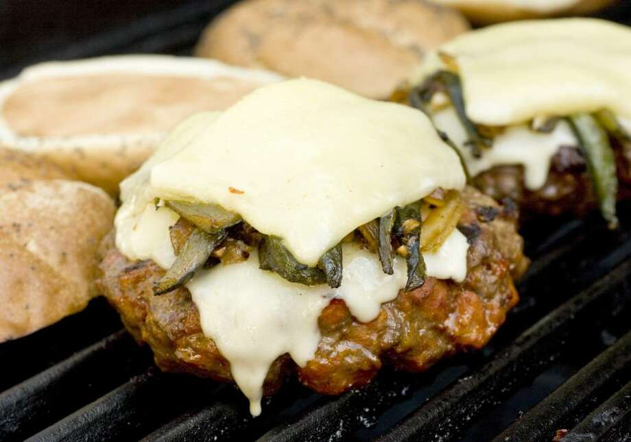 The queso fundido burger by Rick Bayless is seen in this May 23, 2010 photo. Bayless? goal for this burger was simple _ the best of Mexico and the U.S. in one delicious bite.     (AP Photo/Larry Crowe) Photo: Larry Crowe, ASSOCIATED PRESS / AP2010