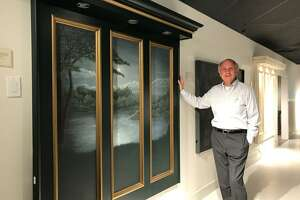 George Holly, director and founder of I.M. Smitten, stands beside the Moon Rising headboard model at the showroom on Trefoil Drive in Trumbull.
