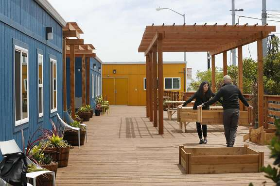 Eoanna Harrison (l to r), San Francisco Department of Public Works, architechtural assistant and Alejandro Pimental, San Francisco Department of Public Works, architechtural associate, set up planters for an edible garden at the Dogpatch Navigation Center on Wednesday, May 24, 2017 in San Francisco, Calif.