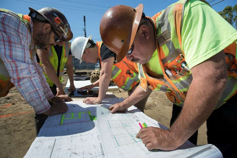 Orozco, Tylee Bussart, Tom Nethery and Jesse Pulido go over plans for the concrete pouring for the building, which will house 228 students. Photo: Paul Kuroda, Special To The Chronicle