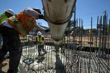Jose Fernandez works the vibrator tool and Noe Orozco directs the chute, pouring about 45 cubic yards of concrete for the base of two elevator shafts at the California College of the Arts' student housing project at 75 Arkansas St. on Tuesday, May 23, 2017 in San Francisco, CA.