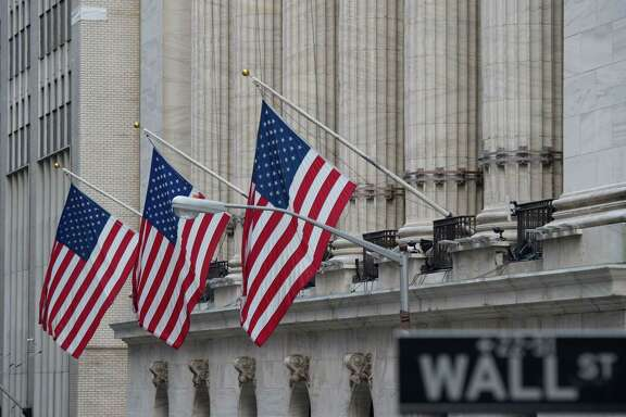 Flags fly outside the New York Stock Exchange in New York. Stocks were slightly higher for most of the day Wednesday as the market kept chipping away at the losses it suffered one week before. Technology companies like TurboTax maker Intuit and materials companies including industrial gas company Praxair made some of the biggest gains.