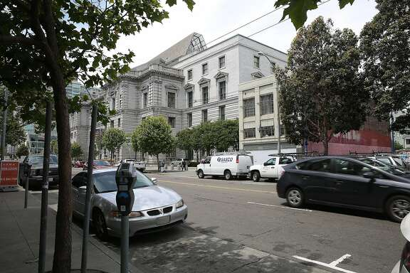 The building at right with neutral facade and red brick alongside is 1068 Mission St. seen right of the courthouse on Wednesday, May 24 , 2017,  in San Francisco, Calif.