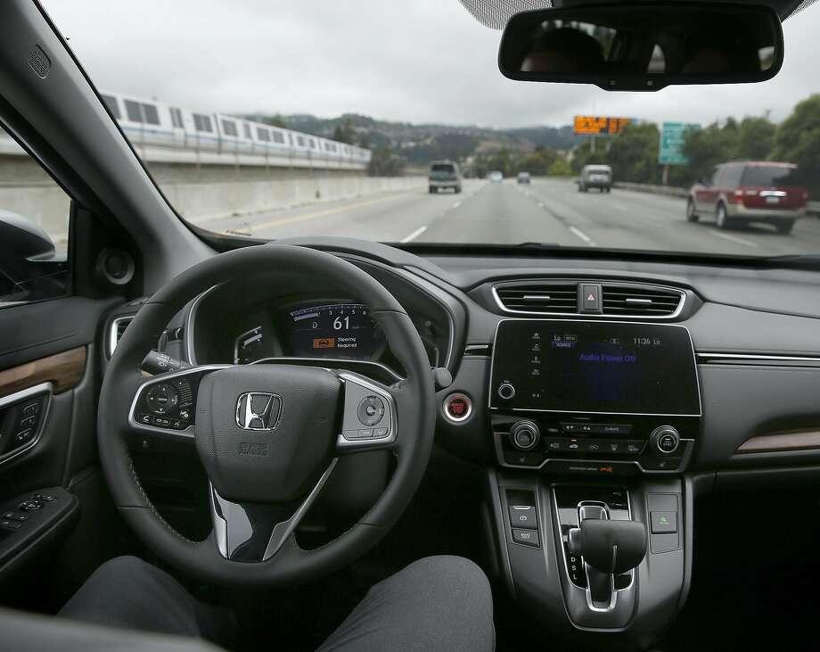 Product specialist Francis Paul Calo (in driver's seat) uses cruise control on a 2017 Honda CRV EXL that has Honda Sensing. Photo: Liz Hafalia, The Chronicle
