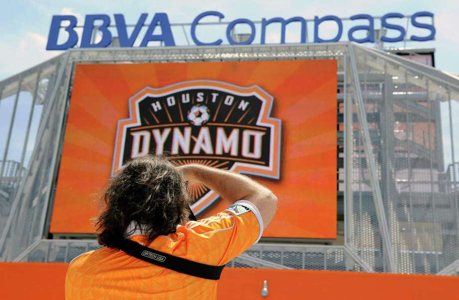 A Houston Dynamo fan takes a picture of the new BBVA Compass stadium before the inaugural soccer game against D.C. United Saturday, May 12, 2012, in Houston. (AP Photo/Pat Sullivan) Photo: Pat Sullivan, STF / AP