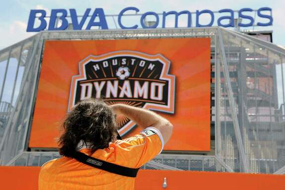 A Houston Dynamo fan takes a picture of the new BBVA Compass stadium before the inaugural soccer game against D.C. United Saturday, May 12, 2012, in Houston. (AP Photo/Pat Sullivan)