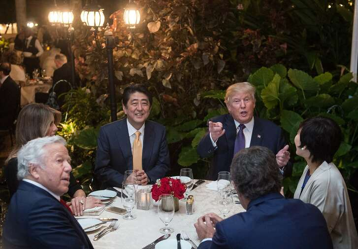US President Donald Trump, Japanese Prime Minister Shinzo Abe (2nd-L), his wife Akie Abe (R), US First Lady Melania Trump (L) and Robert Kraft (2nd-L),owner of the New England Patriots, sit down for dinner at Trump's Mar-a-Lago resort on February 10, 2017.