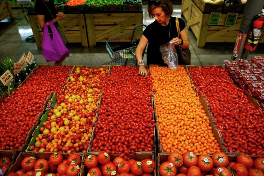 Monica Llobet grabs a handful of tomatoes at Central Market, which underwent a $10 million renovation that was completed this month. Photo: Michael Ciaglo, Staff / Michael Ciaglo