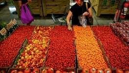 Monica Llobet grabs a handful of tomatoes at Central Market, which underwent a $10 million renovation, Wednesday, May 10, 2017 in Houston.  ( Michael Ciaglo / Houston Chronicle)