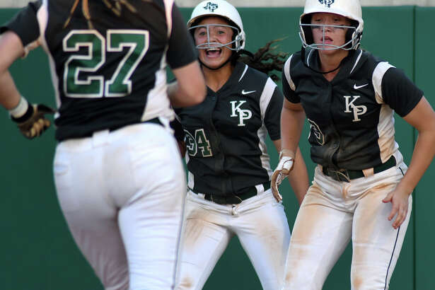Kingwood Park's Nikki Whitehead, left,and MacKenzie Purcell, right, wait for teammate Alyssa Forrester (27) to cross home plate behind them during the Panther's seven-run fifth inning rally against Santa Fe in game 3 of their Region III-5A area round softball playoff series at La Porte High School on May 6, 2017.  (Photo by Jerry Baker/Freelance)