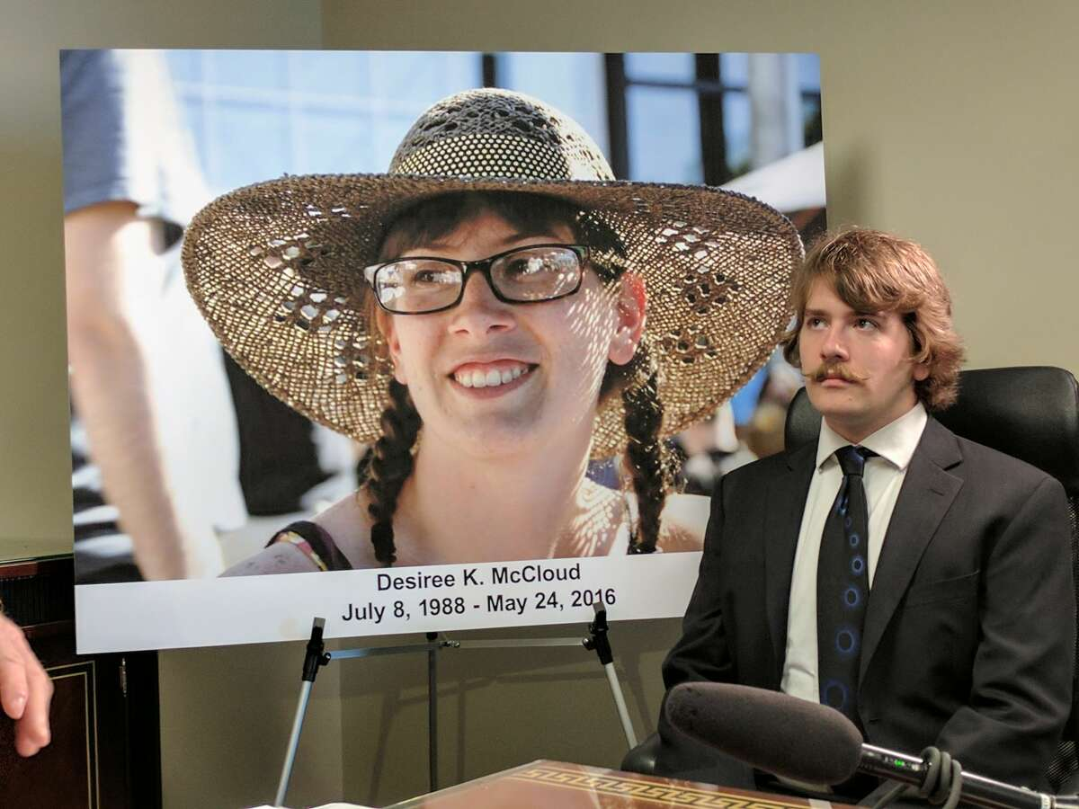 Cody McCloud sits next to a photo of his sister, Desiree McCloud, while attorneys announce a claim against Seattle and Sound Transit for Desiree McCloud's death. Her bicycle got caught in First Hill Streetcar tracks last May, causing her critical head injuries that led to her death 11 days later. Cody McCloud joined another woman injured at the site in suing the city for the hazards the tracks pose to cyclists.