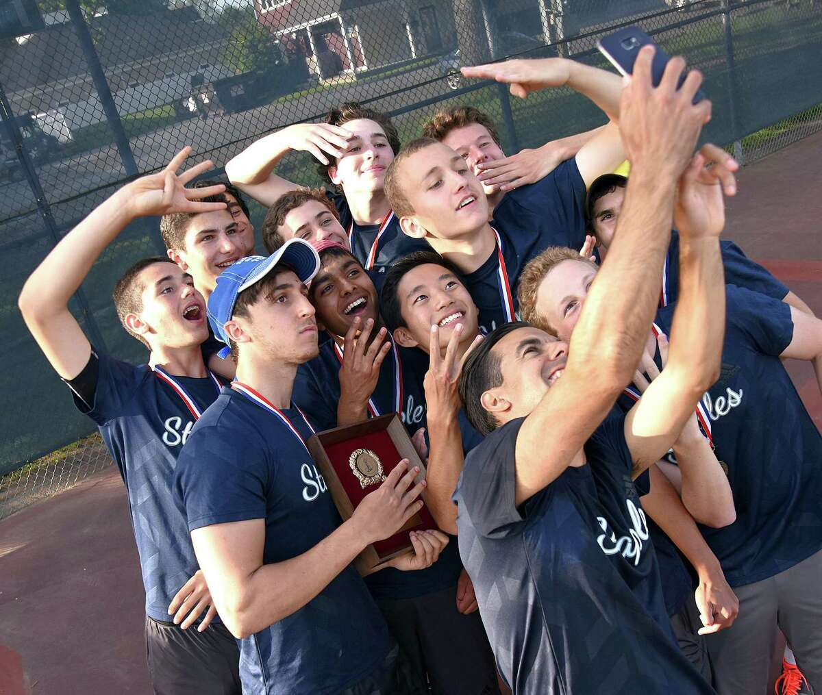 The Staples boys tennis team poses for a selfie with coach Kris Hrisovulos, bottom right, after the Wreckers won their fourth straight FCIAC championship on Wednesday, defeating New Canaan 4-2 at Wilton High School.