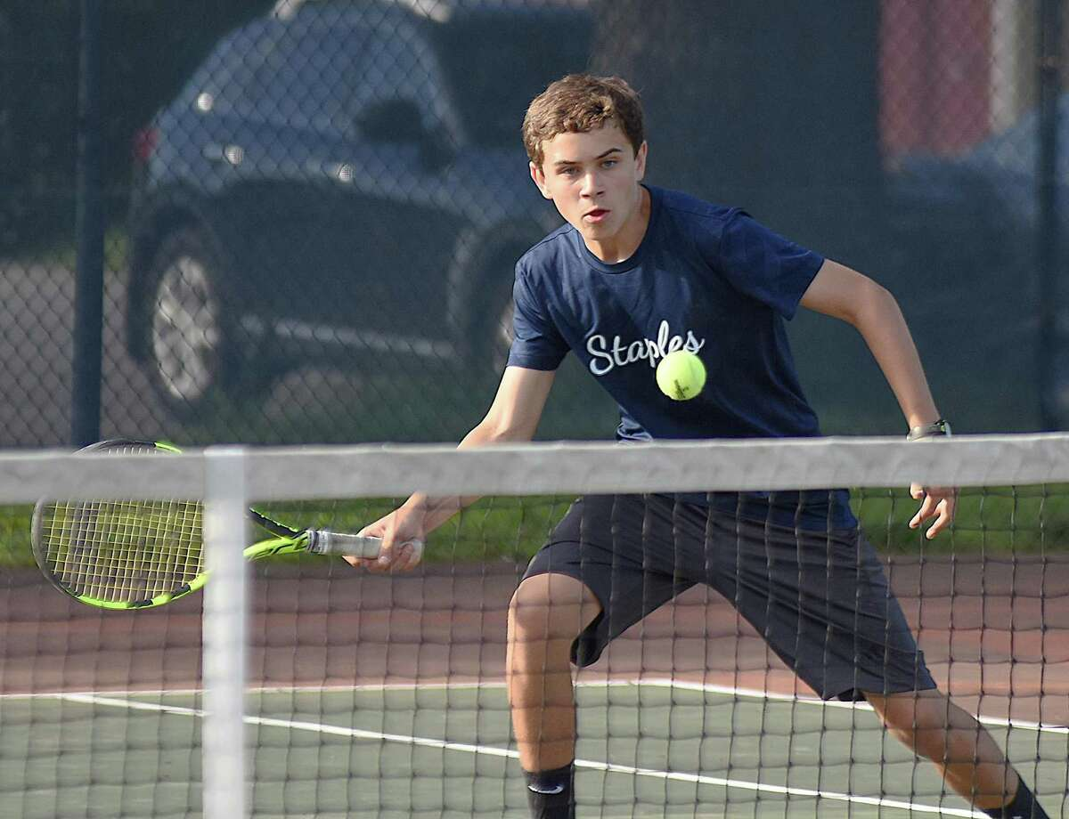 Jack Tooker, a member of the Staples High boys tennis team's seconds doubles squad, keeps his eye on the ball while volleying at the net during Wednesday's FCIAC championship match against New Canaan. Staples won its fourth straight league title with a 4-2 win.