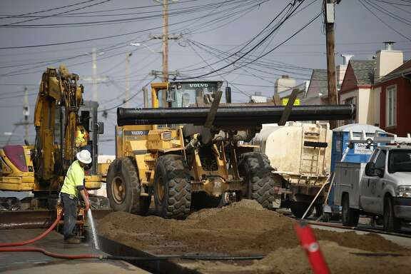 Mauricio Martinez (left), laborer Ranger Pipelines, Inc., sprays water into the ditch where pipelines are being placed as he works on the San Francisco Groundwater Supply Pipeline Project on 41st Avenue between Santiago Street and Taraval Street on Friday, November 21, 2014 in San Francisco, Calif.