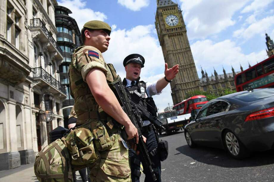A British Army soldier patrols with an armed police officer near the Houses of Parliament in London on Wednesday. Armed forces near landmarks illustrated the gravity of the threat. Photo: JUSTIN TALLIS, Staff / AFP or licensors