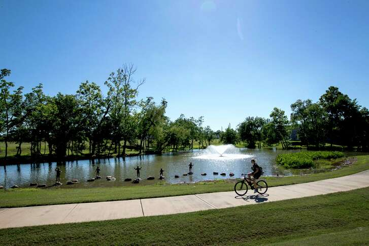 A child rides her bike past a fountain in the Sienna Plantation community, Wednesday, May 24, 2017, in Missouri City. ( Jon Shapley / Houston Chronicle )