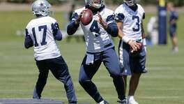 Dallas Cowboys quarterbacks Dak Prescott (4), Kellen Moore (17) and Austin Appleby (3) run through drills during organized team activities at the team's training facility on May 24, 2017, in Frisco.