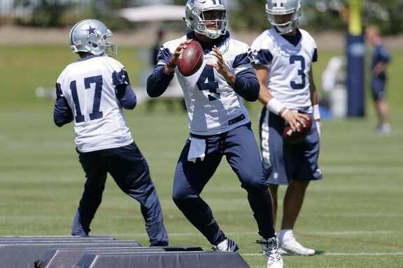 Dallas Cowboys quarterbacks Dak Prescott (4), Kellen Moore (17) and Austin Appleby (3) run through drills during organized team activities at the team's training facility on May 24, 2017, in Frisco.
